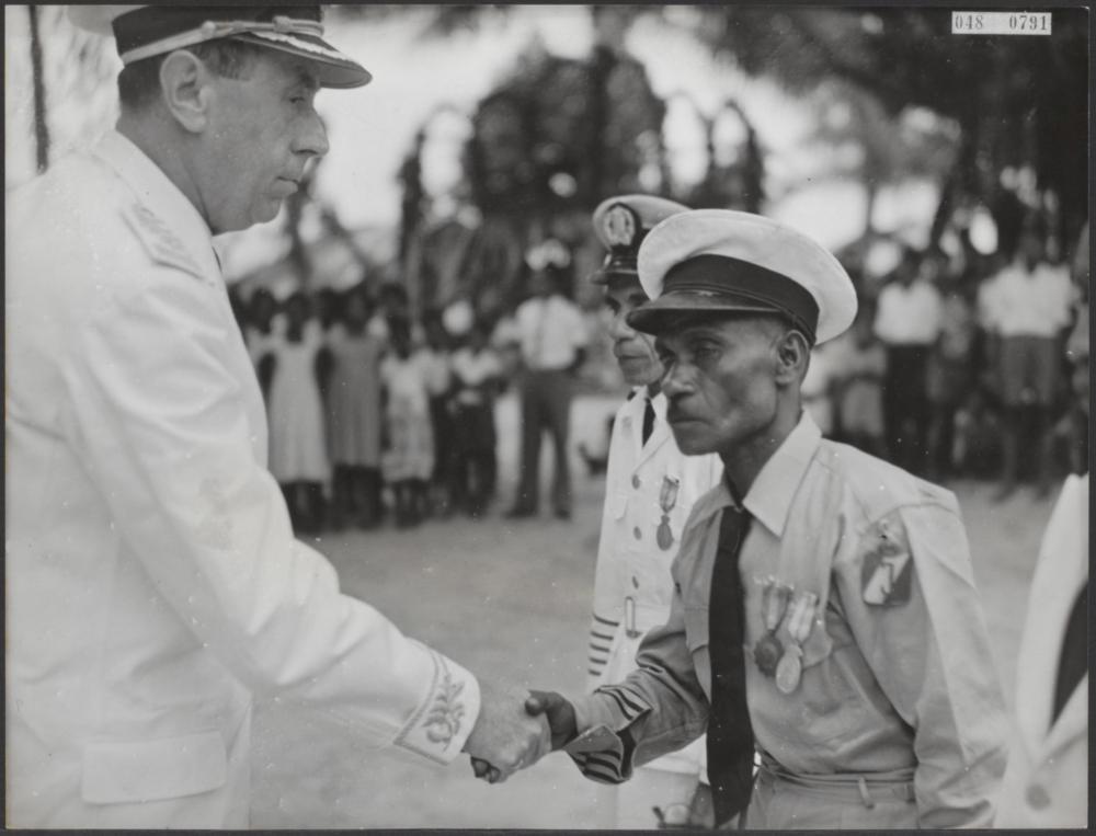 """1957 gouverneur van Nederlands Nieuw-Guinea, dr. J. van Baal (links) reikt koninklijke onderscheidingen uit aan drie van de redders, die vlak na de ramp met de """"Neutron%22 overlevenden uit het water haalden.jpg"""